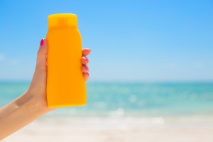 bigstock-Woman-holding-sunscreen-bottle-88434743-300x200